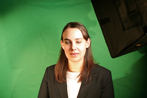 Christine in front of a green screen