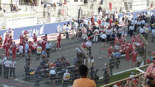 Teams busily work on their cars prior to the start of the 2010 Bahrain Grand Prix.