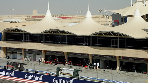 Overlooking the Virgin Racing and Lotus Racing garages in Bahrain pit complex.  The track can be seen weaving its way through the desert in the background.