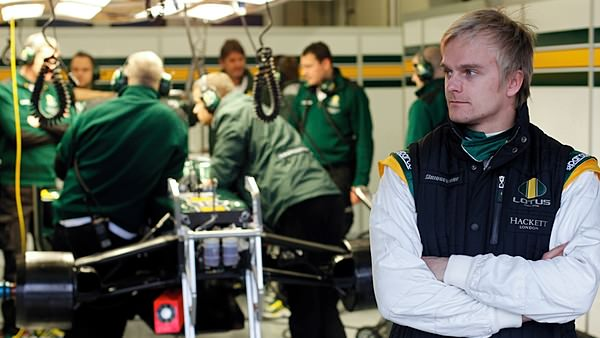 Heikki Kovalainen waits for his mechanics to fix up the Lotus during testing in Jerez