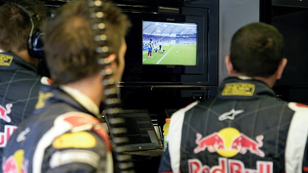 Sidepodcast F1: Red Bull Racing mechanics watch football on the monitors during the Canadian Grand Prix in 2006.
