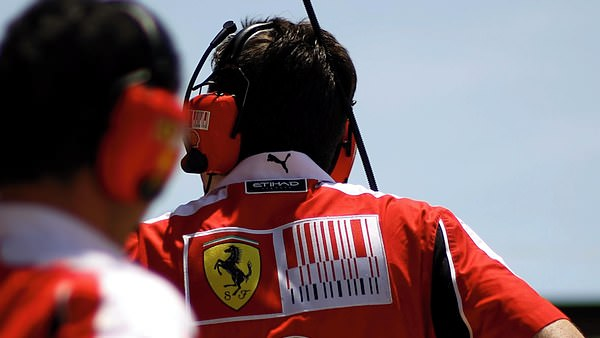 Members of the Ferrari team look on in anticipation.