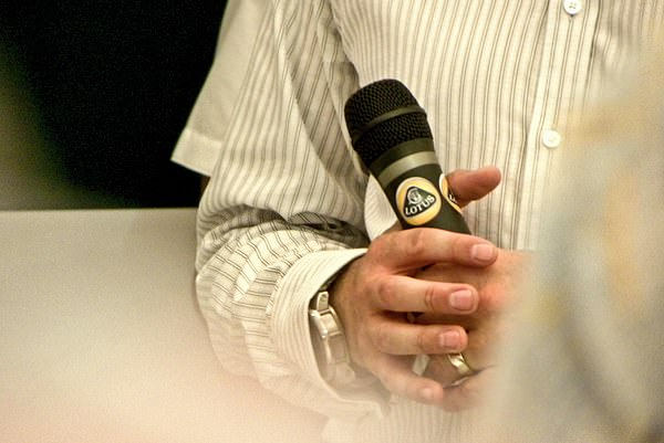 David Croft holds the microphone before interviewing Heikki, Clive Chapman, and Sir Stirling Moss.