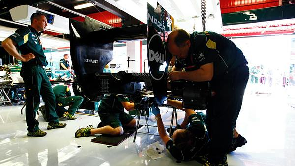 Team Lotus mechanics hard at work preparing their cars in the garage on Thursday
