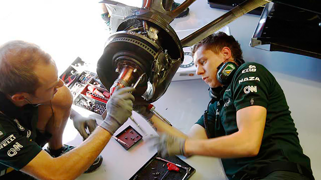 F1 mechanics make adjustments to front wheel hub