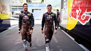 Ricciardo and Verstappen walk to the garage in lederhosen themed overalls
